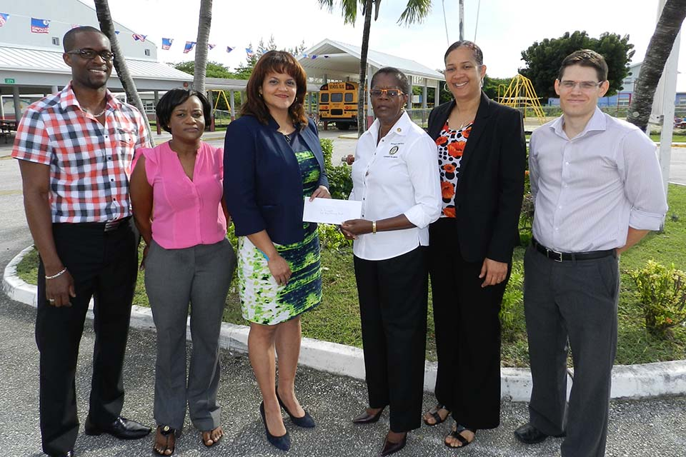 Ms. Desiree Charles (4th from left) presents a donation cheque to Minister for Education Hon. Tara Rivers (4rd from left) to support the Levelled Literacy Intervention Programme at RBPS.  Accompanying them are (left to right) RBPS Teachers Mr. Delton Pedley and Ms. Tamara Dixon, RBPS Principal Mrs. Vickie Frederick and Ministry of Education Literacy Specialist Mr. Brad Wilson.