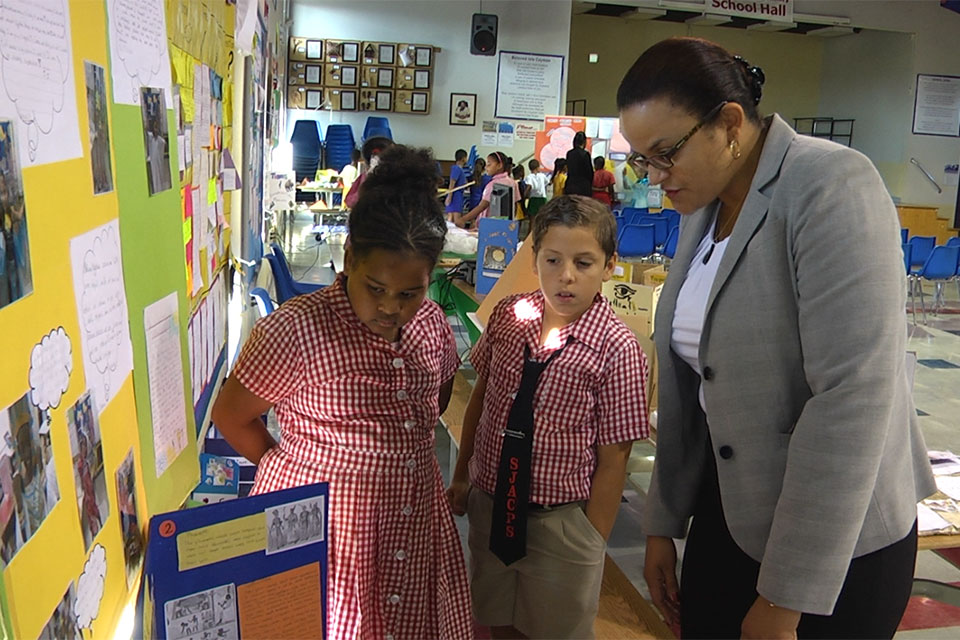 Sir John A. Cumber Primary students proudly explain their project to Minister Tara Rivers.