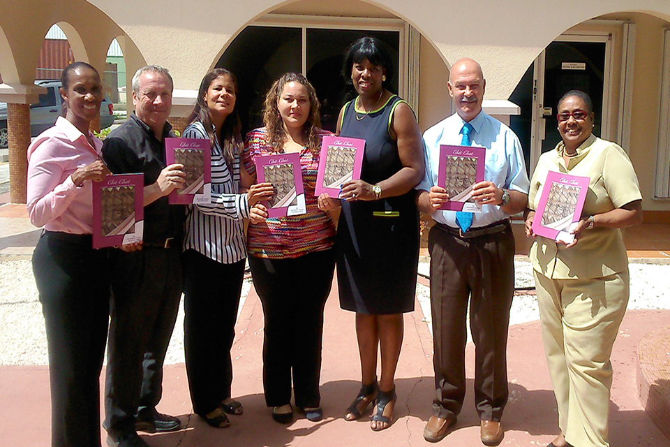 "Author Ms. Alta Bodden-Solomon (centre) presents a copy of the ""Chit Chat"" poetry book to (L to R) Acting Chief Education Officer Ms. Lyneth Monteith, John Gray High School Acting Principal Mr. Matthew Holmes, CIFEC Director Ms. Delores Thompson, Clifton Hunter High School Principal Ms. Pauline Beckford, Senior School Improvement Officer Mr. Roger Morris and Senior School Improvement Officer Mrs. Gloria Bell."