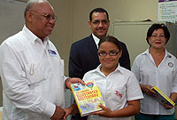 Rotary District Governor Guy Theodore (left) presents an illustrated dictionary to a Year 7 John Gray High School student. Looking on are Education Minister, Hon. Rolston Anglin, JP, and Rotary Sunrise President Andrea Bryan.