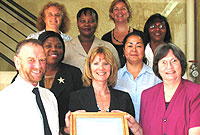 Mrs. Helena McVeigh (front & centre) and the Schools' Inspectorate team receive the Investors in People award.